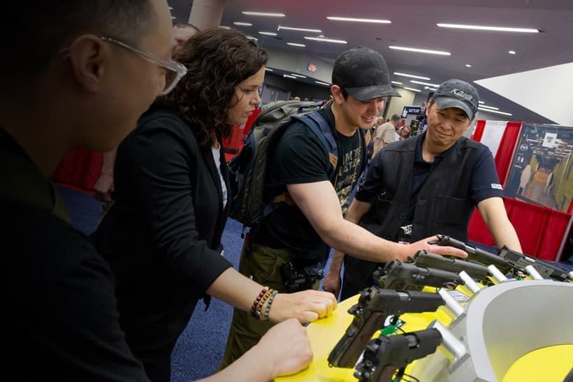 Enthusiasts looking at a firearm display